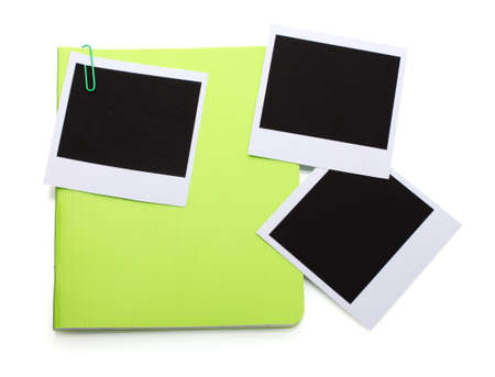 Photo papers and green notebook isolated on white photo