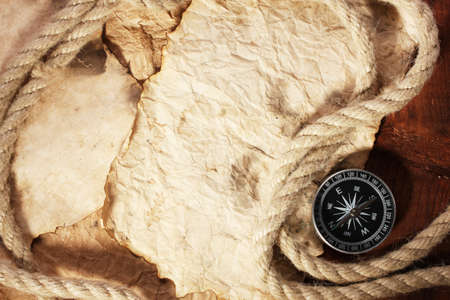 old paper, compass and rope on a wooden table Stock Photo - 11668763