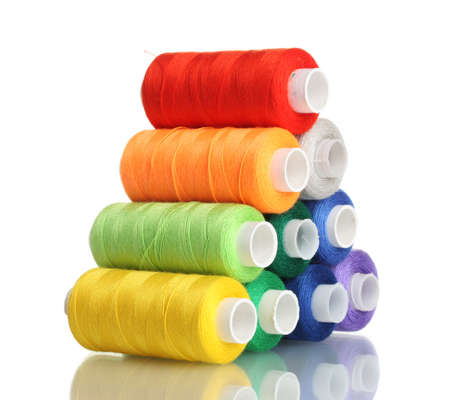Pyramid of many-coloured bobbins of thread isolated on white