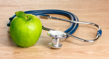 Medical stethoscope and green apple on wooden background photo