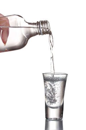 Vodka poured into a glass isolated on white Stock Photo - 11668600
