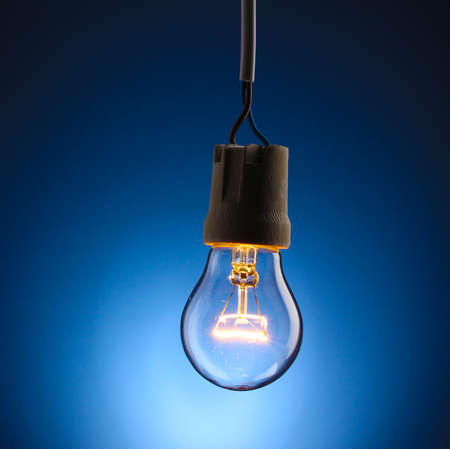 A lit light bulb on blue background photo