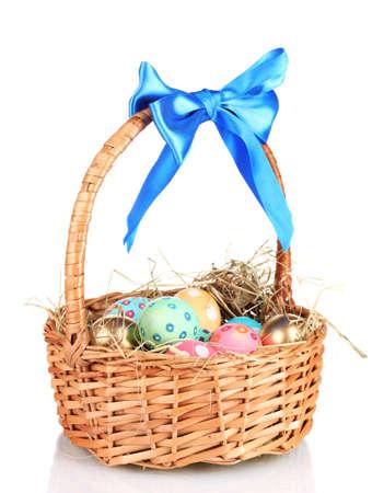 giftbasket: Kleurrijke Pasen eieren in de mand met een blauwe strik op wit wordt geïsoleerd
