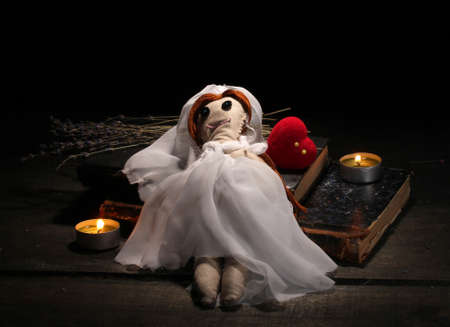 deadman: Voodoo doll girl-bride on a wooden table in the candlelight