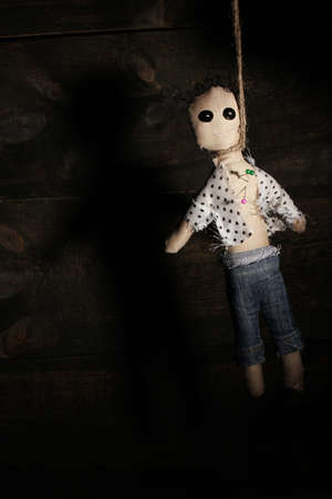 curse: Hanged doll voodoo boy on wooden background Stock Photo