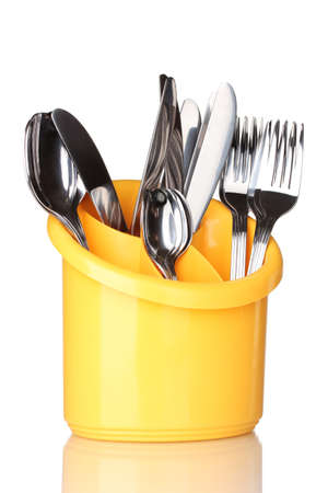 Kitchen cutlery, knives, forks and spoons in yellow stand isolated on white photo