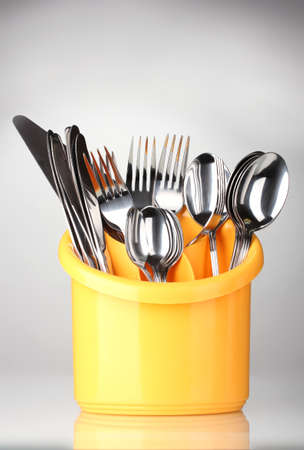 Kitchen cutlery, knives, forks and spoons in yellow stand on grey background photo