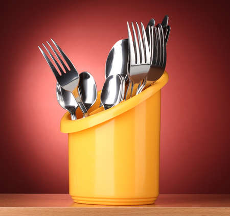 Kitchen cutlery, knives, forks and spoons in yellow stand on red background Stock Photo