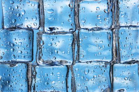 Melting ice cubes on blue closeup photo