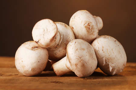 champignons mushrooms in basket on wooden table on brown background photo
