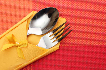 Fork and spoon in a yellow cloth with a bow on a red tablecloth photo