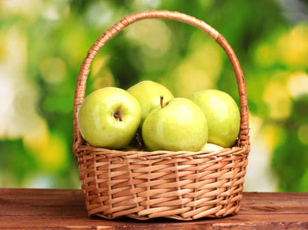 juicy green apples in basket on wooden table on green background photo
