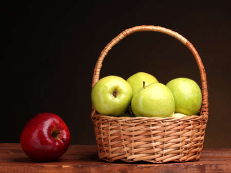 juicy green apples in basket and red apple on wooden table on brown background photo