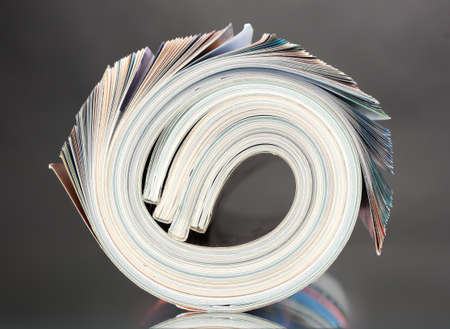 Rolled up magazines on gray background photo