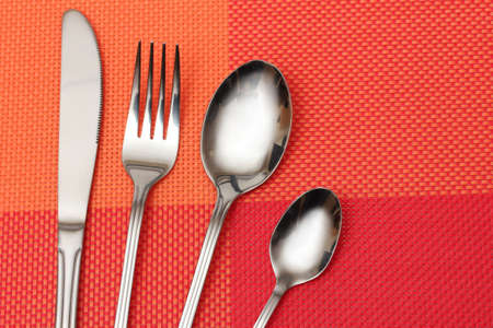 Fork, spoon and knife in a red cloth photo