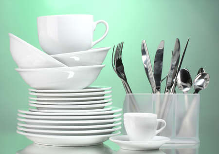 Clean plates, cups and cutlery on green background photo