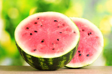Ripe sweet watermelon on wooden table on green  background photo