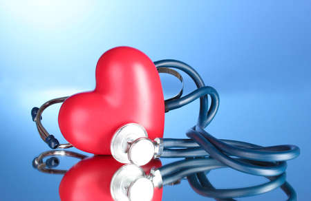 Medical stethoscope and heart  on blue background photo