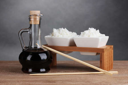 Bowls of cooked rice and soy sauce in jar on wooden table on gray background photo