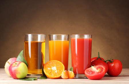 jus orange glazen: Verschillende sappen en fruit op houten tafel op bruine achtergrond