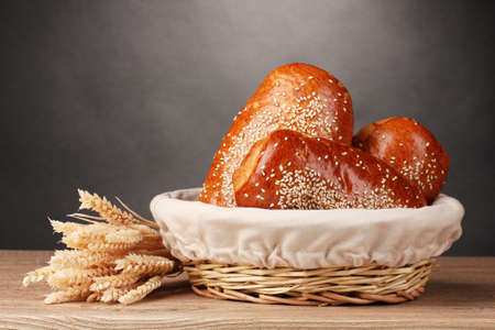 Baked bread in basket on wooden table on grey background photo