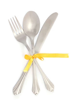 cubiertos de plata: Tenedor de plata y una cuchara, un cuchillo atado con una cinta amarilla aislada en blanco Foto de archivo