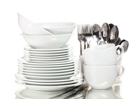 Clean plates, cups and cutlery isolated on white photo
