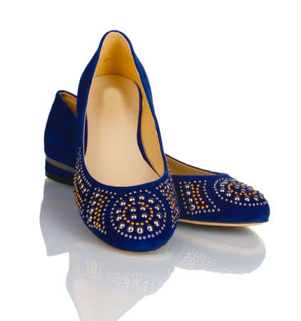 Elegantes zapatos azules planas para las mujeres en piedras aisladas en blanco Foto de archivo