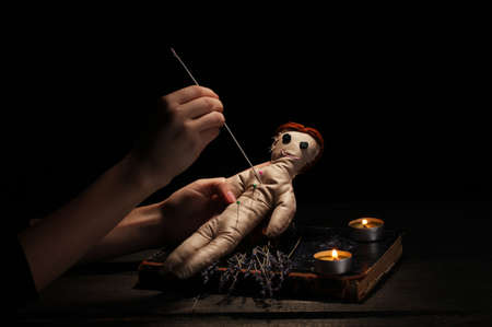 wizardry: Voodoo doll girl pierced by a needle on a wooden table in the candlelight