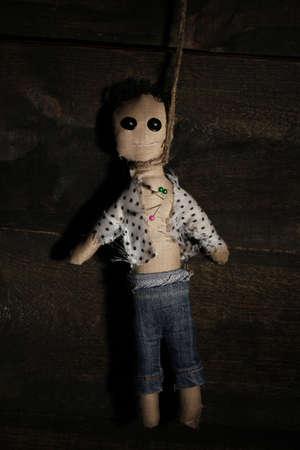 impiccata: Appeso boy bambola voodoo su sfondo di legno