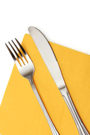 Fork and knife in a yellow cloth isolated on white photo