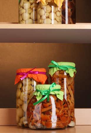 shelfs: delicious marinated mushrooms in the glass jars on wooden shelfs Stock Photo