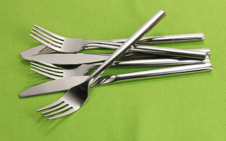 Forks and knives on a green tablecloth photo