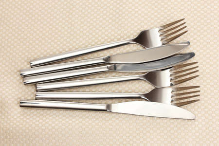 Forks and knives on a beige tablecloth photo