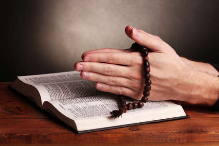Hands holding wooden rosary over open russian holy bible on grey background photo