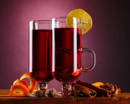mulled wine in the glasses, spice and lemon on purple background photo