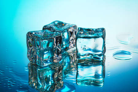 Melting ice cubes on blue background photo