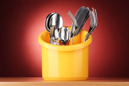 Kitchen cutlery, knives, forks and spoons in yellow stand on red background photo