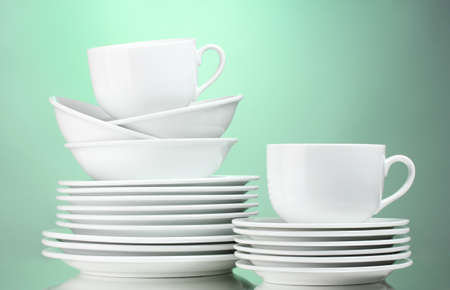 Clean plates, cups on green background photo