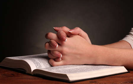 Hands folded in prayer over open russian Holy Bible on black background photo