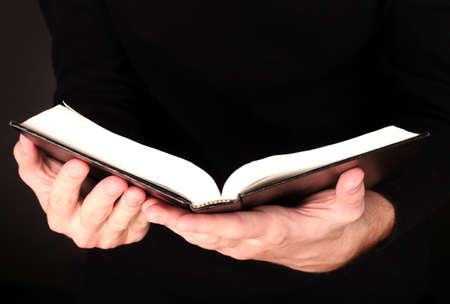 open bible: Hands holding open russian bible on black background