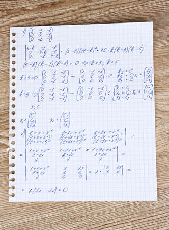 Math on copybook page on a wooden table photo