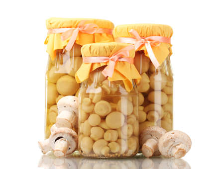 delicious marinated mushrooms in the glass jars and raw champignons isolated on white photo