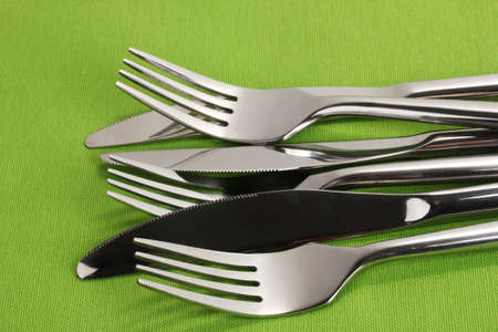 Forks and knives on a green tablecloth closeup photo