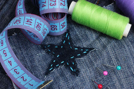 Star-shaped patch on jeans with threads and buttons closeup Stock Photo - 11904798