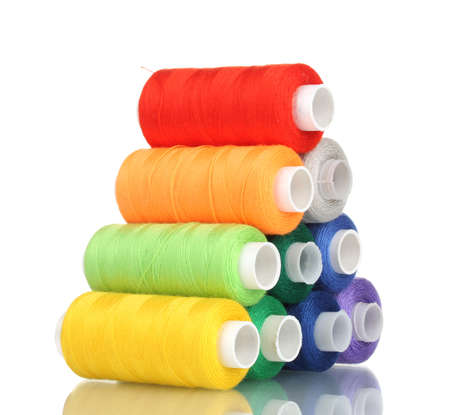 bobbin: Pyramid of many-coloured bobbins of thread isolated on white