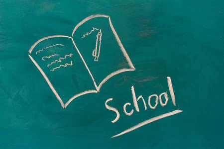 Blackboard with drawing book closeup photo