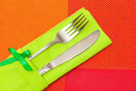 Fork and knife in a green cloth with a bow on a red tablecloth photo