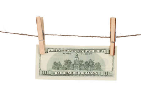 One hundred dollar bills is hanging on a rope with wooden clothespin isolated on white photo
