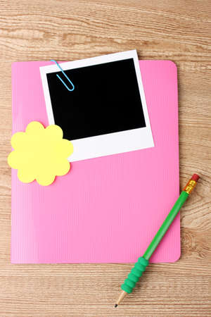 Photo paper and pink notebook on wooden background photo